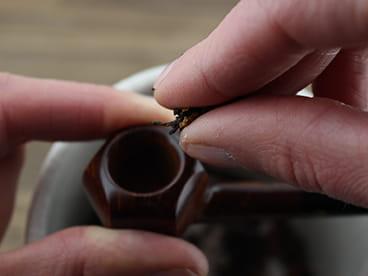 Insérer une pincée de tabac dans le foyer de ma pipe